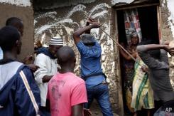 Demonstrators corner a suspected member of the ruling party's Imbonerakure youth militia at his home in the Cibitoke district of Bujumbura, Burundi, Thursday May 7, 2015. (AP Photo/Jerome Delay)