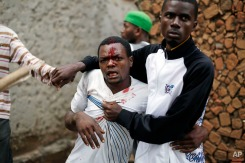 Jean Claude Niyonzima, a suspected member of the ruling party's Imbonerakure youth militia, is restrained as a mob gathers around his house, as protests continue against President Pierre Nkurunziza's decision to seek a third term in office in the Cibitoke district of Bujumbura, Burundi, Thursday May 7, 2015. (AP Photo/Jerome Delay)