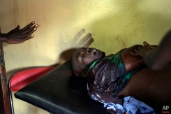 A demonstrator seriously wounded by live ammunition waits for treatment in a small clinic in the Musaga district of Bujumbura, Burundi, Monday May 4, 2015. (AP Photo/Jerome Delay)