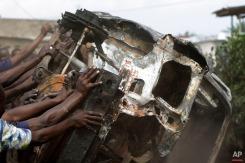 Demonstrators topple a burnt out car in the Musaga neighborhood of Bujumbura, Burundi, Friday May 1, 2015. (AP Photo/Jerome Delay)