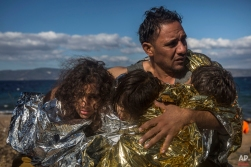 A man holds three children wearing thermal blankets after their arrival in bad weather from Turkey on the Greek island of Lesbos , Wednesday, Oct. 28, 2015. (AP Photo/Santi Palacios)