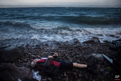 The lifeless body of an elderly unidentified man is seen on the beach after washing up on the shoreline at the village of Skala, on the Greek island of Lesbos, on Sunday, Nov. 1, 2015. (AP Photo/Santi Palacios)