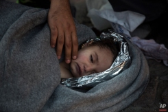 Paramedics and doctors care for a baby girl after a boat with refugees and migrants sunk while was crossing the Aegean sea from Turkey to the Greek island of Lesbos on Wednesday, Oct. 28, 2015. The condition of the child is not known. (AP Photo/Santi Palacios)