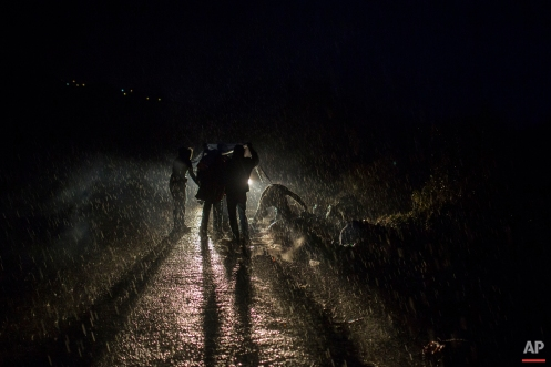 Refugees wait under the rain for a bus, transferring them to a processing center, in Skala Sikaminias village, on the northeastern Greek island of Lesbos, early Thursday, Oct. 22, 2015. (AP Photo/Santi Palacios)