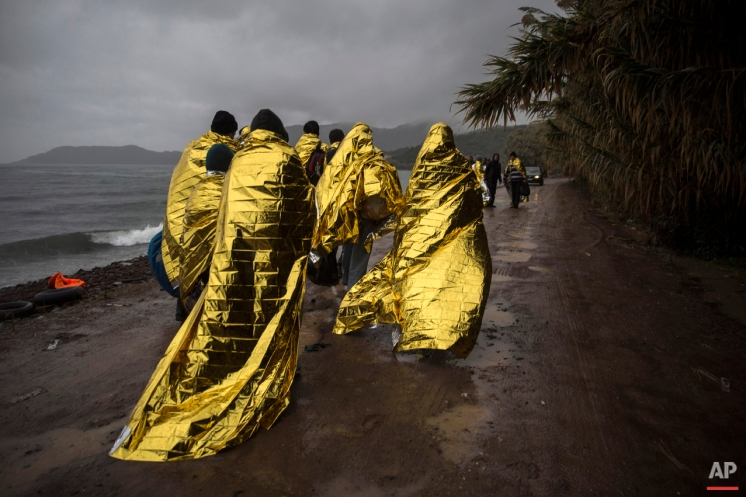 Refugees and migrants are covered with thermal blankets after their arrival on a dinghy from the Turkish coast to the Skala Sykaminias village on the northeastern Greek island of Lesbos, Friday, Oct. 23, 2015. (AP Photo/Santi Palacios)