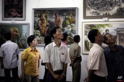 North Koreans look at paintings on display, Sunday, July 26, 2015, in Pyongyang, North Korea. The art exhibition comprised of works by different local artists on the life of North Koreans during the Japanese occupation and before their country's liberation from the Korean War. (AP Photo/Maye-E Wong)