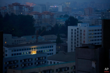 In this Friday, May 8, 2015 photo, portraits of the late North Korean leaders Kim Il Sung, left, and Kim Jong Il, right, glow on the facade of a building as dusk descends upon Pyongyang, North Korea. In Pyongyang, commercial advertisements are rarely seen in public, but portraits of the late leaders and propaganda slogans are a common sight on buildings and along the streets. (AP Photo/Maye-E Wong)