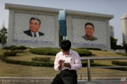In this Tuesday, May 5, 2015, photo, a man sits in front of portraits of the late North Korean leaders Kim Il Sung, left, and Kim Jong Il, right, as he uses his smartphone in Pyongyang, North Korea. North Korean officials have unveiled a mobile-friendly online shopping site. (AP Photo/Maye-E Wong)
