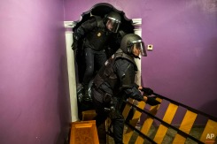 Police enter the apartment of Emilia Montoya Vazquez by forcing their way in between furniture after they broke down the main door to evict her and her family in Madrid, Spain, Wednesday, Feb. 25, 2015. Montoya, who lived with her son and daughter in law, both unemployed, and three grandchildren of 7, 6, 3 years old, had accumulated a debt with the (EMV) City Hall Housing Company as she could not afford to pay rent due to her only income which is a state benefit of 460 euros ($522) a month. The eviction was carried out in spite dozens of housing right activists who gathered inside the apartment and blocked the main door. EMVS, a state company with an aim to give housing solutions for people in need, sold 1.860 state apartments to private investors, last year. (AP Photo/Andres Kudacki)