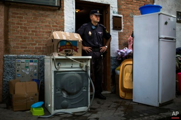"""Police block the apartment's entrance as Amalio Barrul Gimenez' belongings lay on the street after Amalio and his family's got evicted in Madrid, Spain, Tuesday, June 24, 2014. Amalio Barrul Gimenez, , 41 years old, his wife Isabel Morales Bachiller, 35 years old, 2 month pregnant, and three children live with a low income coming from selling goods in the street and state benefits of 530 euros ($720). They occupied Bankia Bank apartment one and a half year ago and have tried to negotiate to pay a low rent but the bank demanded their eviction. The eviction was carried out in spite of the Victims' Mortgage Platform (PAH). Banners read """"Shame"""" """"you are laughing and we are suffering"""", """"three children in the street"""", """"a pregnant woman evicted"""", """"extra payment to evict people"""". (AP Photo/Andres Kudacki)"""