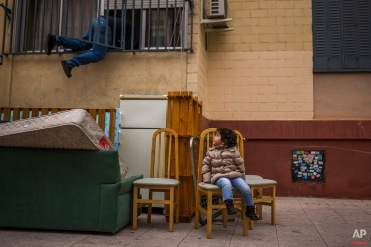 In this picture taken Wednesday, Feb. 11, 2015, Diana Sofia Meliton, 2 years old, sits outside together with belongings after her and her family got evicted by the police and watches a housing right activist re-opening her apartment for them to live in Madrid, Spain. Pablo Enrique Meliton, 39 years old, his wife Damaris Varela Rivera, 36 yeas old , and their daughter Diana Sofia Meliton, 2 years old, rent a room in a occupied Bankia bank apartment one year ago as they could not afford to pay rent and stay occupying the apartment after the rest of the occupants left. They have now an income of euro 790 ($893) and they have tried to negotiate to pay a low rent but the Bankia bank demanded their eviction. Housing right activists tried to stop the process but the police evicted the family.(AP Photo/Andres Kudacki)