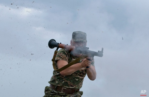 Series chronicling the continuing war in Ukraine. A pro-Russian rebel fires a rocket propelled grenade on the rooftop of an apartment building during clashes with Ukrainian troops on the outskirts of Luhansk, Ukraine, Monday, June 2, 2014. Hundreds of pro-Russia insurgents attacked the border guard base in eastern Ukraine on Monday. (AP Photo/Vadim Ghirda)
