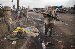 A Russia-backed rebel looks at the flag covered body of an Ukrainian serviceman in Debaltseve, Ukraine, Friday, Feb. 20, 2015. (AP Photo/Vadim Ghirda)