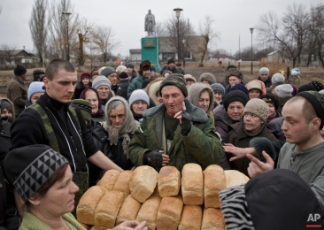 """A man speaks to a crowd of residents warning them not to push as they wait to get bread, one per person, baked by Russia-backed separatists in Chornukhyne, Ukraine, Monday, March 2, 2015. More than 6,000 people have died in eastern Ukraine since the start of the conflict almost a year ago that has led to a """"merciless devastation of civilian lives and infrastructure,"""" the U.N. human rights office said Monday. (AP Photo/Vadim Ghirda)"""