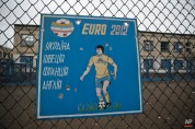 The Euro 2012 soccer championship Group D teams, Ukraine, Sweden, France and England are listed on a bullet riddled metal sheet attached to the fence of the inmates sports area inside the destroyed prison in Chornukhyne, Ukraine, Monday, March 2, 2015. (AP Photo/Vadim Ghirda)