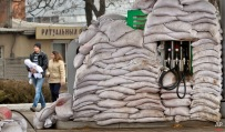 A couple and baby walk past a fuel pump covered in sandbags to protect it from possible shelling, in Donetsk, Ukraine, Monday, March 2, 2015. (AP Photo/Vadim Ghirda)