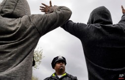 A member of the Baltimore Police Department stands guard outside of the department's Western District police station as men hold their hands up in protest during march for Freddie Gray, Wednesday, April 22, 2015, in Baltimore. (AP Photo/Patrick Semansky)