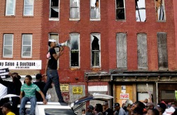 Blighted buildings stand behind a protester as he leads marchers in a chant from atop a vehicle, Saturday, May 2, 2015, in Baltimore. (AP Photo/Patrick Semansky)