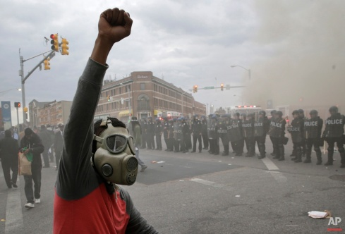 A demonstrator raises his fist as police stand in formation and a CVS store burns, Monday, April 27, 2015, during unrest following the funeral of Freddie Gray in Baltimore. (AP Photo/Patrick Semansky)