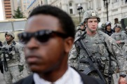 A member of the Maryland National Guard stands guard outside Baltimore City Hall as marchers protest the death of Freddie Gray, Wednesday, April 29, 2015, in Baltimore. (AP Photo/Patrick Semansky)