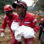 A fireman carries the body of a child recovered from the site of a landslide in Cambray, a neighborhood in the suburb of Santa Catarina Pinula, about 10 miles east of Guatemala City, Friday, Oct. 2, 2015. The hill that towers over Cambray collapsed late Thursday after heavy rains, burying homes with dirt, mud and rocks. (AP Photo/Moises Castillo)