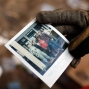 A fireman holds a photo of an unidentified family as he searches the site of a mudslide in Cambray, a neighborhood in the suburb of Santa Catarina Pinula, on the outskirts of Guatemala City, Saturday, Oct. 3, 2015. Rescue workers recovered more bodies Saturday after a hillside collapsed on homes late Thursday, while more are feared still buried in the rubble. (AP Photo/Luis Soto)