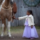 """In this Sept.20, 2015 photo, girl Alessandra Fortes de Lima, 6, touches the boot of her father Adimir Goncalves de Lima, 49, before a parade during the Semana Farroupilha or """"Ragamuffin"""" week, in Alegrete municipality, Rio Grande do Sul state, Brazil. Some of the Brazilian cowboys ride with little girls wearing old-fashioned dresses. They parade before crowds in southern Rio Grande do Sul state, which fancies itself as practically a separate nation, with its rugged rural traditions and Germanic roots. (AP Photo/Eraldo Peres)"""