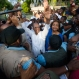 Haiti's former President Jean Bertrand Aristide, center, waves to the crowd after he urged supporters to vote for presidential candidate Maryse Narcisse, center right, of the Fanmi Lavalas political party, in Port-au-Prince, Haiti, Wednesday Sept. 30, 2015. Aristide's public endorsement could be a boon for Narcisse, who is polling well below front-runner Jude Celestin. During the last election cycle about five years ago, the party was barred from the ballot. (AP Photo/Dieu Nalio Chery)