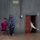Residents stand outside their flooded house in Zoatlan, Nayarit state, some 150 km northwest of Guadalajara, Mexico, Saturday, Oct. 24, 2015. Hurricane Patricia made landfall Friday on a sparsely populated stretch of Mexico's Pacific coast as a Category 5 storm, avoiding direct hits on the resort city of Puerto Vallarta and major port city of Manzanillo as it weakened to tropical storm force while dumping torrential rains that authorities warned could cause deadly floods and mudslides. (AP Photo/Eduardo Verdugo)