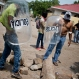 Masked miners and their family members, some holding police shields, patrol a road block they set up in their neighborhood in El Limon, Nicaragua, Wednesday, Oct. 7, 2015. Clashes between police and miners erupted Tuesday when police tried to remove roadblocks set up all over town by miners who went on strike two weeks ago to protest the firing of several of their union members by the Canadian mine company B2Gold. According to police, one officer died in the violence. (AP Photo/Esteban Felix)