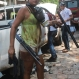 A woman carries a shotgun, gas mask and baton taken from a riot police officer after clashes between striking miners and riot police in El Limon, Nicaragua, Tuesday, Oct. 6, 2015. The miners where protesting against the firing of several union members by the Canadian B2Gold gold mining company when the clashes erupted. According to the police one police officer died in the violence. (Eddy Lopez/La Prensa via AP)
