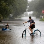 Will Cunningham, 14, rides his bike down Station 29 on Sullivan's Island, S.C., with his friend Patrick Kelly, 14, going the kayak route during flood waters on Sullivan's Island Saturday, Oct. 3, 2015. Rain pummeling parts of the East Coast showed little sign of slackening Saturday, with record-setting precipitation prolonging the soppy misery that has been eased only by news that powerful Hurricane Joaquin will not hit the U.S. (AP Photo/Mic Smith)
