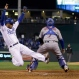 Kansas City Royals' Alcides Escobar, left, scores past New York Mets catcher Travis d'Arnaud on a single by Eric Hosmer during the fifth inning of Game 2 of the Major League Baseball World Series Wednesday, Oct. 28, 2015, in Kansas City, Mo. (AP Photo/Matt Slocum)
