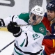 Dallas Stars left wing Antoine Roussel (21) bats the puck as he is guarded by Florida Panthers defenseman Willie Mitchell (33) during the first period of an NHL hockey game, Saturday, Oct. 17, 2015 in Sunrise, Fla. (AP Photo/Wilfredo Lee)