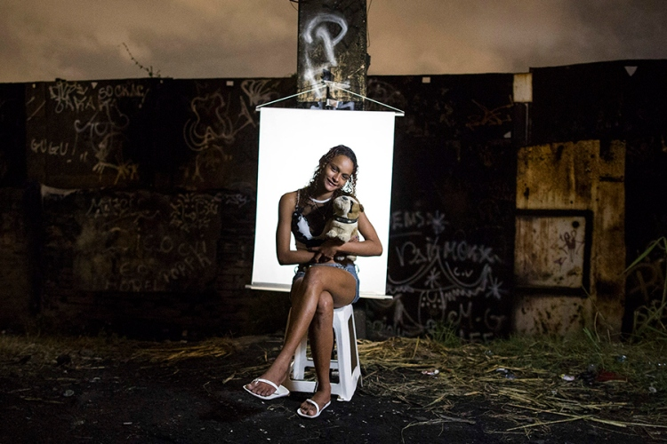 """In this March 18, 2015 photo, Ketellin Silva 17, poses for a portrait in an open-air crack cocaine market, known as a """"cracolandia"""" or crackland, where users can buy crack, and smoke it in plain sight, day or night, in Rio de Janeiro, Brazil. Silva, the mother of a 3-year-old girl, holds a stuffed toy dog she says belongs to her premature infant son who remains hospitalized. (AP Photo/Felipe Dana)"""