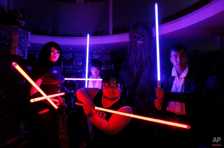 "In this Dec. 14, 2015, photo, 32-year-old Tsai Jung-chou, center, also known as ""Makoto Tsai"", poses with friends as they wield his handcrafted replicas of the Star Wars lightsaber at his home workshop in New Taipei City, Taiwan. A former optical engineer, Tsai now designs and fabricates his own versions of the iconic sci-fi weapon which he sells for up to $400 per model. (AP Photo/Wally Santana)"