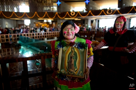 A clown holds a picture of the Virgin of Guadalupe, as she arrives for a mass at the Basilica of Our Lady of Guadalupe in Mexico City, Monday, Dec. 14, 2015. Hundreds of clowns belonging to various clown associations made their annual pilgrimage to the Basilica on Monday to pay their respects to the Virgin of Guadalupe, Mexico's patron saint. (AP Photo/Rebecca Blackwell)