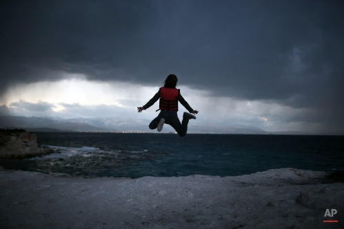 A migrant boy jumps in the air as he waits to travel to Greek islands by dinghies, near Cesme, Izmir, Turkey, late Thursday Dec. 31, 2015. More than a million people hoping to escape war and poverty have made their way into Europe this year, according to migration monitors, but attention has been focused on two more common routes ó across the Aegean Sea from Turkey to Greece or across the Mediterranean from Libya to Italy. (AP Photo/Emre Tazegul)