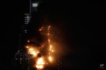 Smoke and flames pouring from a residential building, which also contains the Address Downtown Hotel, in Dubai, United Arab Emirates, Thursday evening, Dec. 31, 2015. (AP Photo/Sunday Alamba)