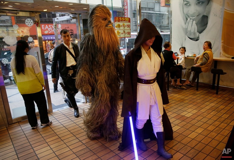 "In this Dec. 14, 2015, photo, Star Wars fans dressed in character enter a fast food restaurant in the neighborhood of 32-year-old Tsai Jung-chou, also known as ""Makoto Tsai"", who makes replica lightsabers at his home workshop in New Taipei City, Taiwan.  A former optical engineer, Tsai now designs and fabricates his own versions of the iconic sci-fi weapon which he sells for up to $400 per model. (AP Photo/Wally Santana)"