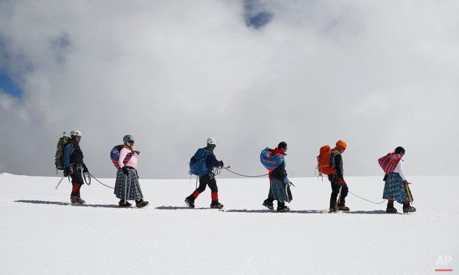 In this Dec. 17, 2015 photo, Aymara indigenous women descend the Huayna Potosi mountain with their husbands, who work as professional guides, on the outskirts of El Alto, Bolivia. Eleven women, ranging in age from 20 to 50 years old, made the two-day climb up the mountain. All of the women work as porters and cooks at the base camp, but six of the youngest ones would like to eventually join the ranks of the men and guide tourists to the peak. (AP Photo/Juan Karita)