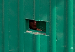 """A guard peers out of a hole in the entrance gate to the Agujas immigration detention center, where U.S. fugitive Ethan Couch is being detained in Mexico City, Thursday, Dec. 31, 2015. The Texas teen known for using an """"affluenza"""" defense in a fatal drunken-driving accident is being held at a Mexico City immigration detention center in one of the capital's poorest areas, where he will likely spend weeks, if not months, as he appeals deportation. (AP Photo/Rebecca Blackwell)"""