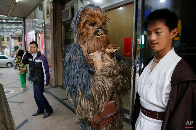 "In this Dec. 14, 2015, photo, Star Wars fans dressed as Chewbacca and Luke Skywalker leave a fast food restaurant in the neighborhood of 32-year-old Tsai Jung-chou, also known as ""Makoto Tsai"", who makes replica lightsabers at his home workshop in New Taipei City, Taiwan. A former optical engineer, Tsai now designs and fabricates his own versions of the iconic sci-fi weapon which he sells for up to $400 per model. (AP Photo/Wally Santana)"