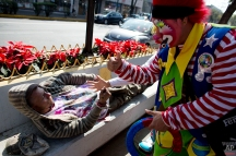 Clowns stop to high five a man who was sleeping on a bench wearing a tee-shirt with an image of Jesus, in Mexico City, Monday, Dec. 14, 2015. Hundreds of clowns belonging to various clown associations made their annual pilgrimage to the Basilica on Monday to pay their respects to the Virgin of Guadalupe, Mexico's patron saint. (AP Photo/Rebecca Blackwell)