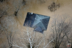 In this aerial photo, floodwater reaches the rooftop of a house, Thursday, Dec. 31, 2015, in Valley Park, Mo. Surging Midwestern rivers forced hundreds of evacuations, threatened dozens of levees and brought transportation by car, boat or train to a virtual standstill Thursday in the St. Louis area. (AP Photo/Jeff Roberson)