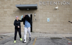 TCU quarterback Trevone Boykin, right, holds a jacket over his head as he is escorted from a detention center after he was released on bail, Thursday, Dec. 31, 2015, in San Antonio. Police charged Boykin with felony assault of a police officer stemming from a bar fight early Thursday morning. TCU football coach Gary Patterson has suspended Boykin for Saturday's Alamo Bowl game against Oregon. (AP Photo/Eric Gay)