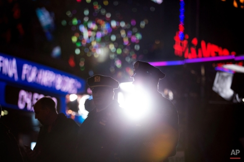 New York police officers keep watch along police lines during the hours leading up to the annual New Year's Eve celebration in Times Square, Thursday, Dec. 31, 2015, in New York. Nearly 6,000 armed police officers are guarding Times Square as the year 2015 draws to a close. (AP Photo/Kevin Hagen)