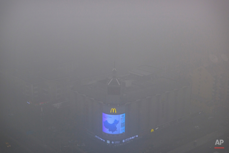 A video display on the side of a building shows a map of China amid heavy pollution and fog in Beijing, Tuesday, Dec. 1, 2015. Schools in Beijing were ordered to keep students indoors Tuesday after record-breaking air pollution in the Chinese capital soared to up to 35 times the safety levels. (AP Photo/Mark Schiefelbein)