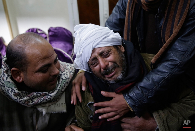 In this Monday, Feb. 16, 2015 photo, a man is comforted by others as he mourns over Egyptian Coptic Christians who were captured in Libya and killed by militants affiliated with the Islamic State group, outside of the Virgin Mary church in the village of el-Aour, near Minya, 220 kilometers (135 miles) south of Cairo, Egypt. Egyptian warplanes struck Islamic State targets in Libya on Monday in swift retribution for the extremists' beheading of a group of Egyptian Christian hostages on a beach, shown in a grisly online video released hours earlier. (AP Photo/Hassan Ammar)
