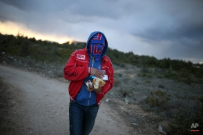 A migrant walks after he received free food as he waits to travel to Greek islands by dinghies, near Cesme, Izmir, Turkey, late Thursday Dec. 31, 2015. More than a million people hoping to escape war and poverty have made their way into Europe this year, according to migration monitors, but attention has been focused on two more common routes across the Aegean Sea from Turkey to Greece or across the Mediterranean from Libya to Italy. (AP Photo/Emre Tazegul)